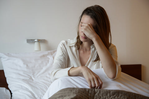 Woman having a headache resting in bed
