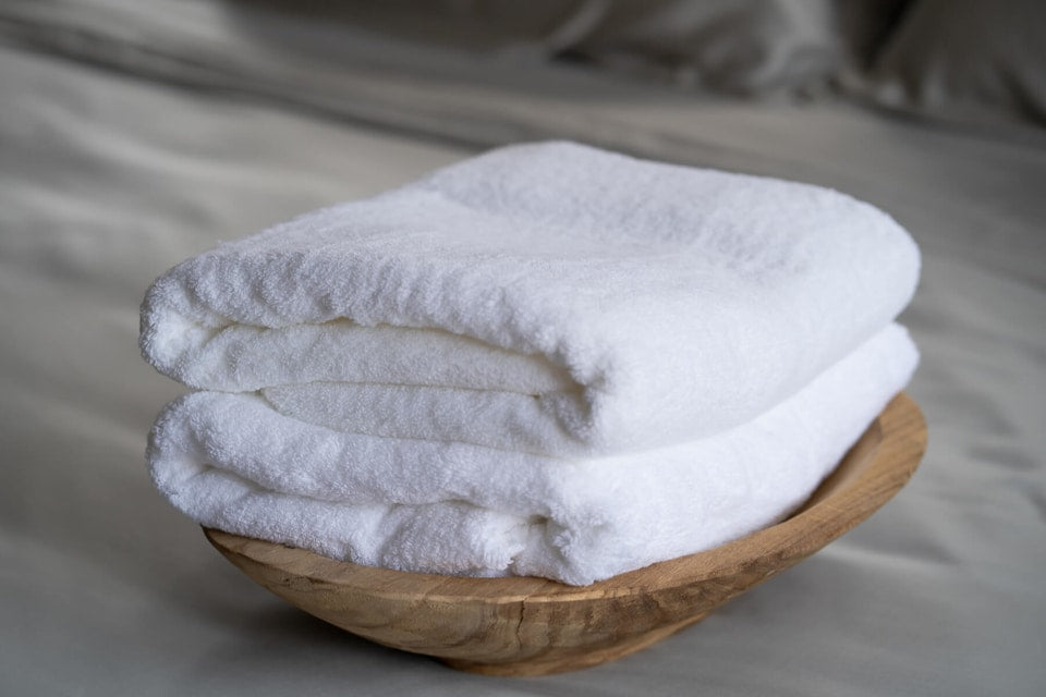 stack of white cotton bath towels in a wooden bowl