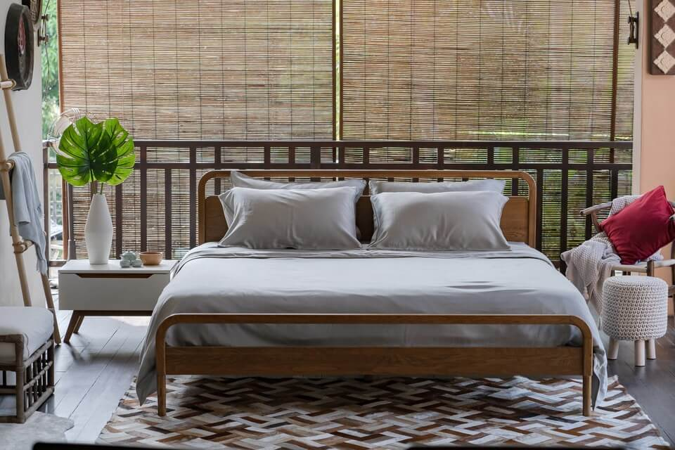 light grey tencel bed sheets and four pillows on a king bed