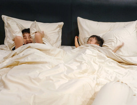 happy kids enjoying cotton sheets in bed