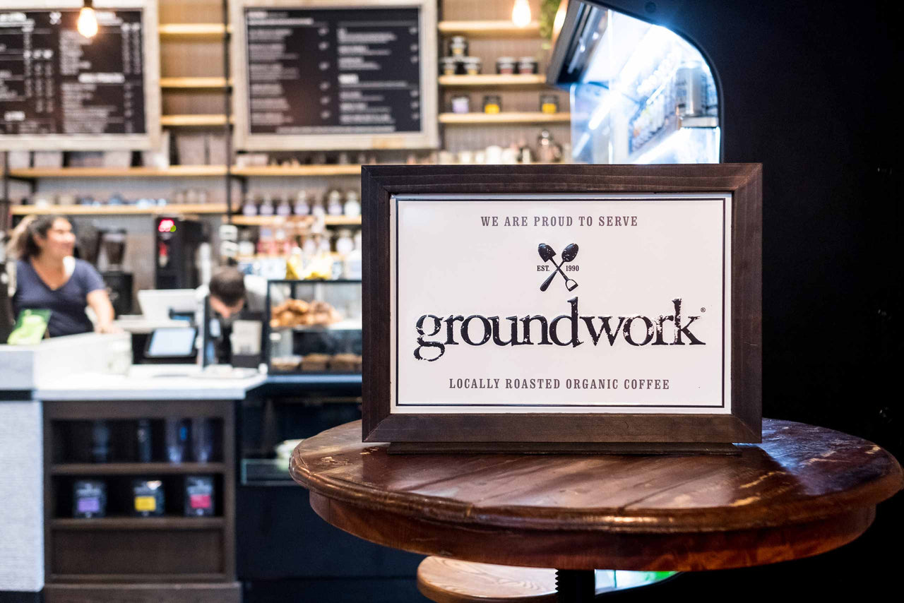 Groundwork sign in front of cafe counter with people
