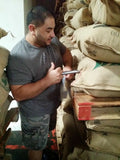 Edgar using a trier to pull samples of green coffee beans.