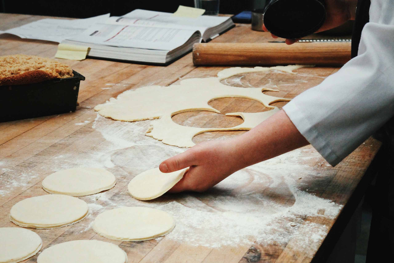 baker rolling and cutting dough