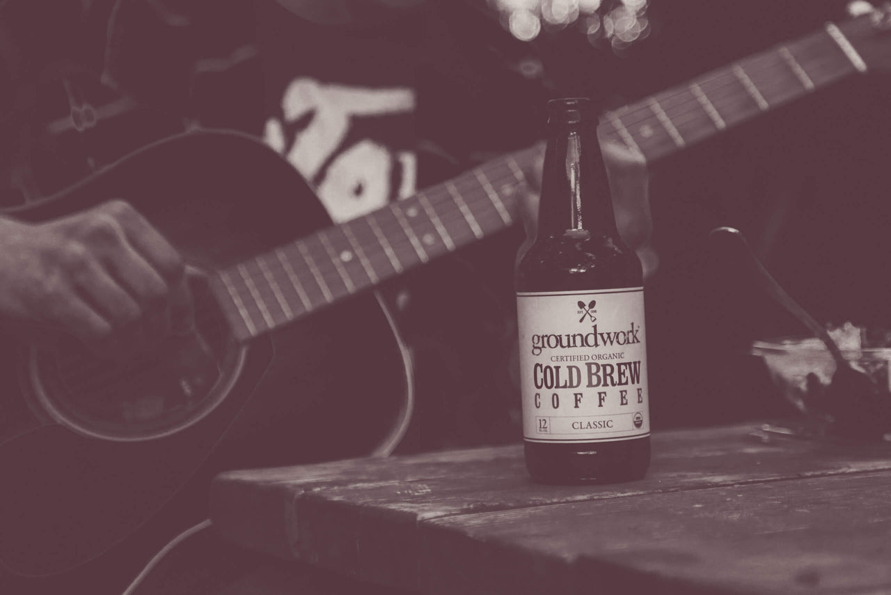 acoustic guitar being played behind a bottle of Groundwork Cold Brew