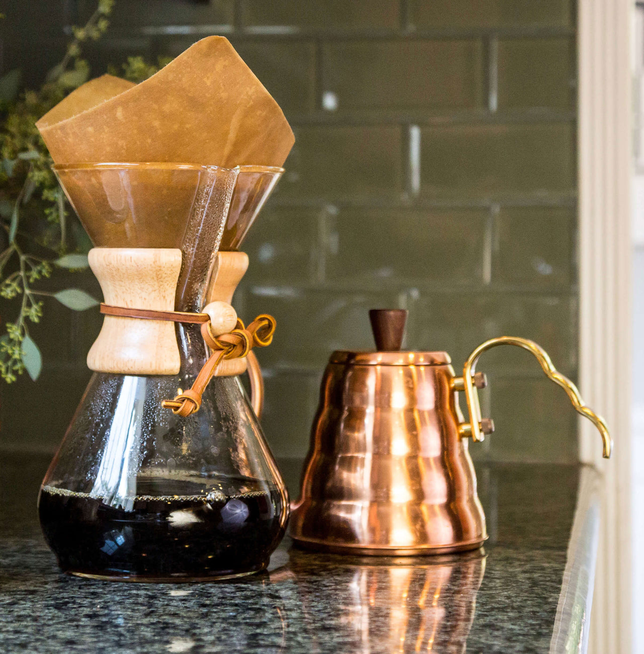 chemex fill with coffee next to brass kettle on counter