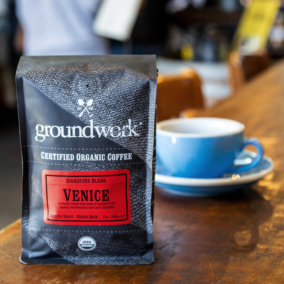 bag of Groundwork's Venice coffee on table with blue cup