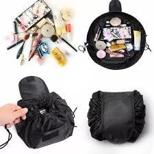 A drawstring cosmetic bag in black. There are skin products and makeup inside the bag.