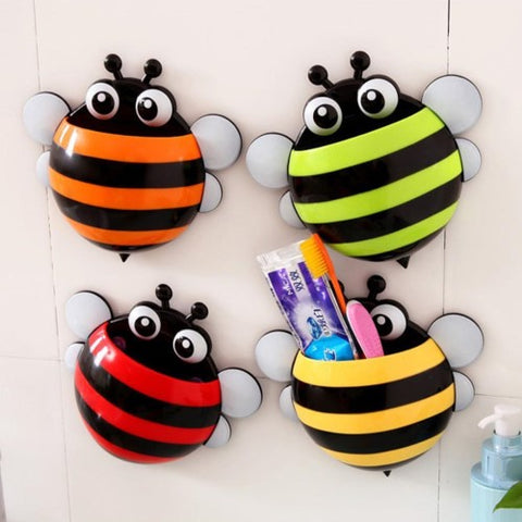 Assorted colour bee toothbrush holders on a wall. The yellow be has toothpaste and toothbrushes inside.