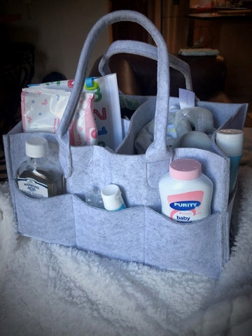 Grey felt nappy organiser with other baby accessories