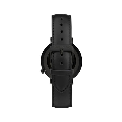 Matte black and black watch with a stitched black genuine leather band and matte black buckle designed by THE HOUND, styled done up and shot from behind.