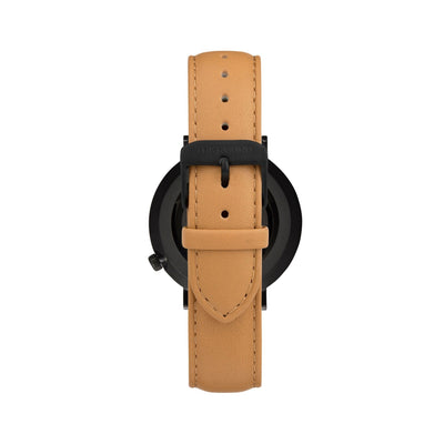 Matte black and black watch with a stitched camel genuine leather band and matte black buckle designed by THE HOUND, styled done up and shot from behind.