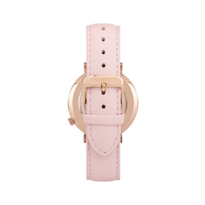 Rose gold and white watch with a stitched blush pink genuine leather band and rose gold black buckle designed by THE HOUND, styled done up and shot from behind.