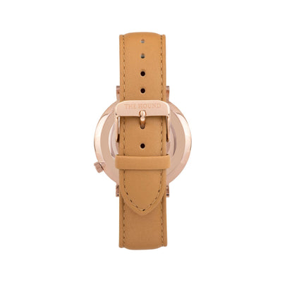 Rose gold and white watch with a stitched camel genuine leather band and rose gold black buckle designed by THE HOUND, styled done up and shot from behind.