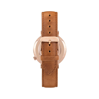 Rose gold and white watch with a stitched tan genuine leather band and rose gold black buckle designed by THE HOUND, styled done up and shot from behind.