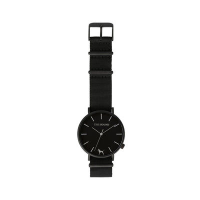 Matte black and black watch with a soft black nato band and matte black buckle designed by THE HOUND, styled flat and shot from above.