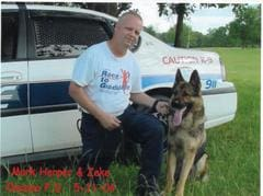 Mark and Zeke, a German Shepherd Police Dog, posing during training in front of a police car