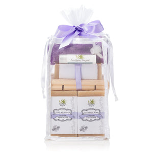 A picture of a natural bath and body gift bag with a purple bow on top from Southern Natural and contains soap, dead sea bath salt, a wooden soap dish, and a mesh soap sock.