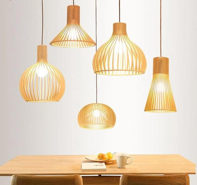 A collection of Japandi-inspired pendant lamps that combine the elevated minimalism of both Japanese and Scandinavian designs. Five different styles of the pendant lamp are featured in a dining room space. The wooden and bamboo silhouettes of these stunning lamps resemble traditional Japanese bird cages, and shine a light on understated sophistication.