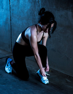 Woman in her twenties or thirties preparing for a workout. Tanned, dark hair, fit. Wearing a black bralette and black leggings, with white Nike trainers. She is crouched and tying her shoe laces.