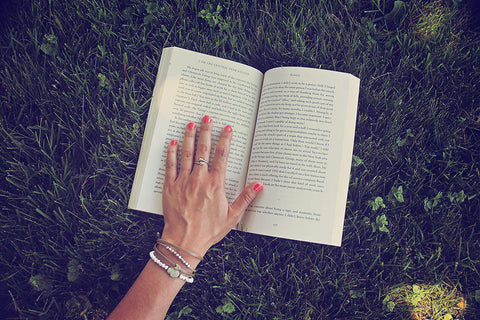 2021 summer reading list - hand on book, wearing bracelets by Peacock and Lime