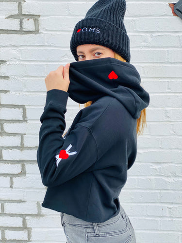 Woman wearing black crop women's hoodie with embroidered symbol on the left arm, and small red heart embroidered on the hood. Black wool beanie with Heart-OMS logo embroidered on the front.