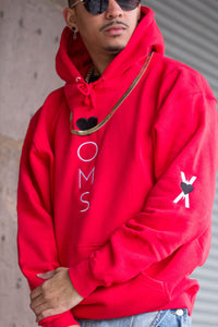 "Man wearing red hoodie with heart-oms logo vertically embroidered down the front, and ""heart on my sleeve"" screenprinted down the righta arm."