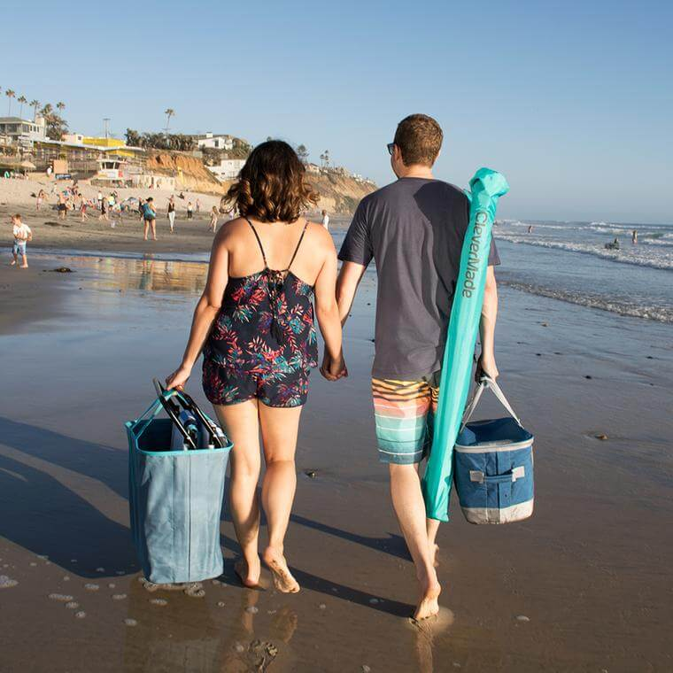 man and woman walking on the beach carrying a QuadraBrella
