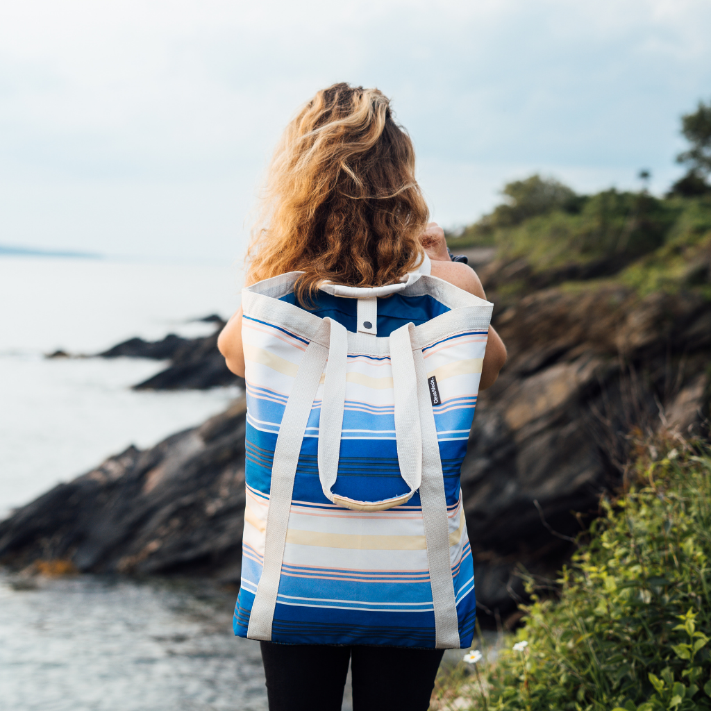 Girl standing with CleverMade BackSak Beach Tote on her back overlooking the ocean