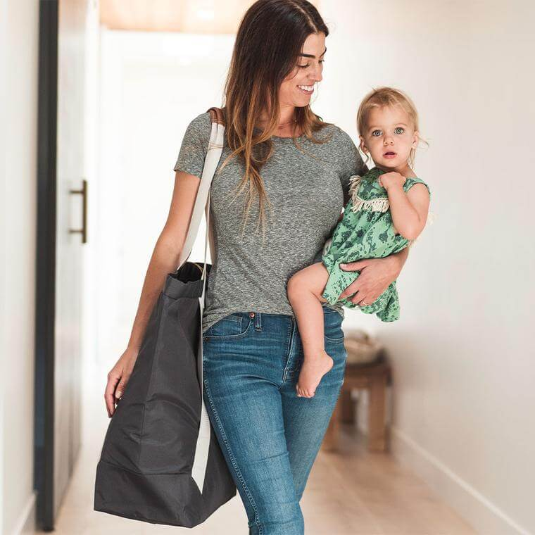 woman carrying a baby and the Laundry Backsack LUXE in Charcoal