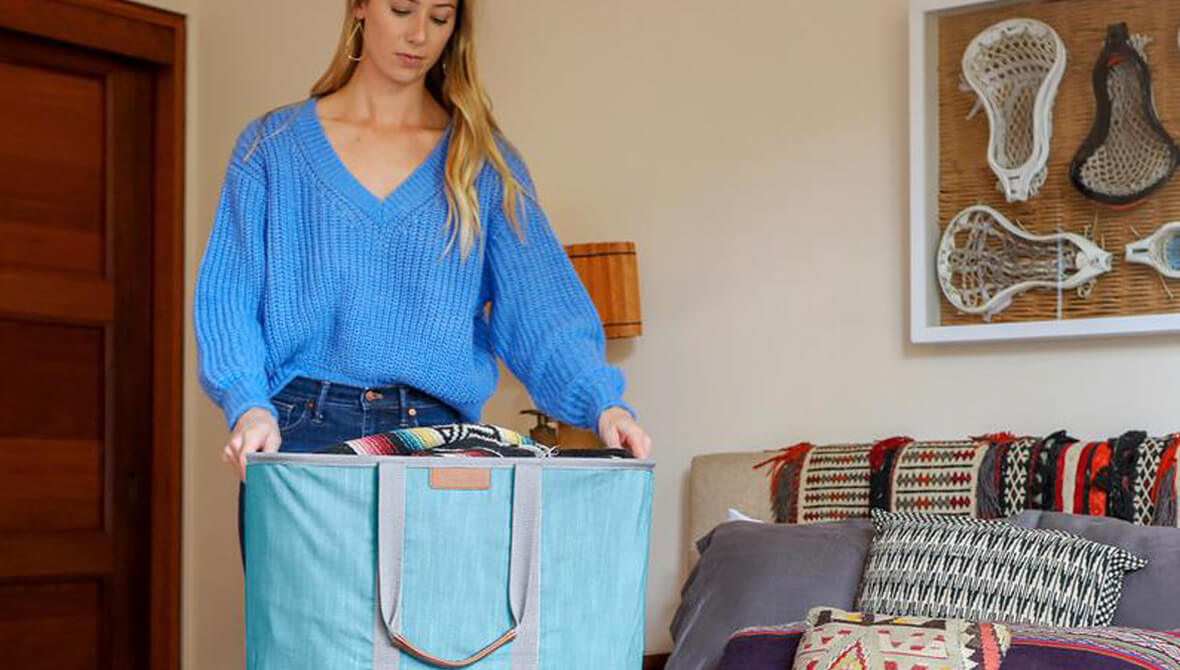 woman in bedroom with full Laundry Caddy LUXE