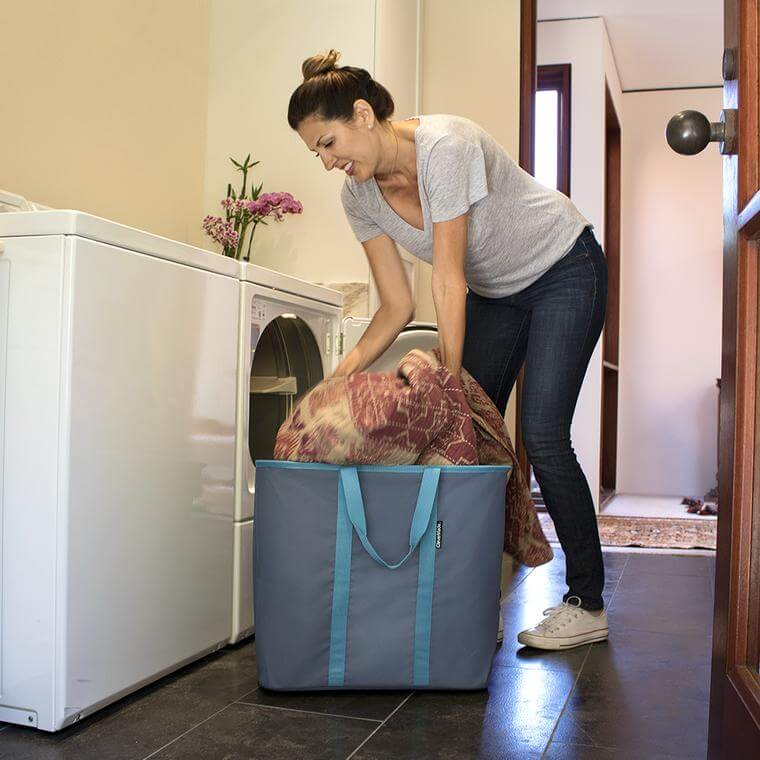 woman filling the Laundry Caddy with clean blankets