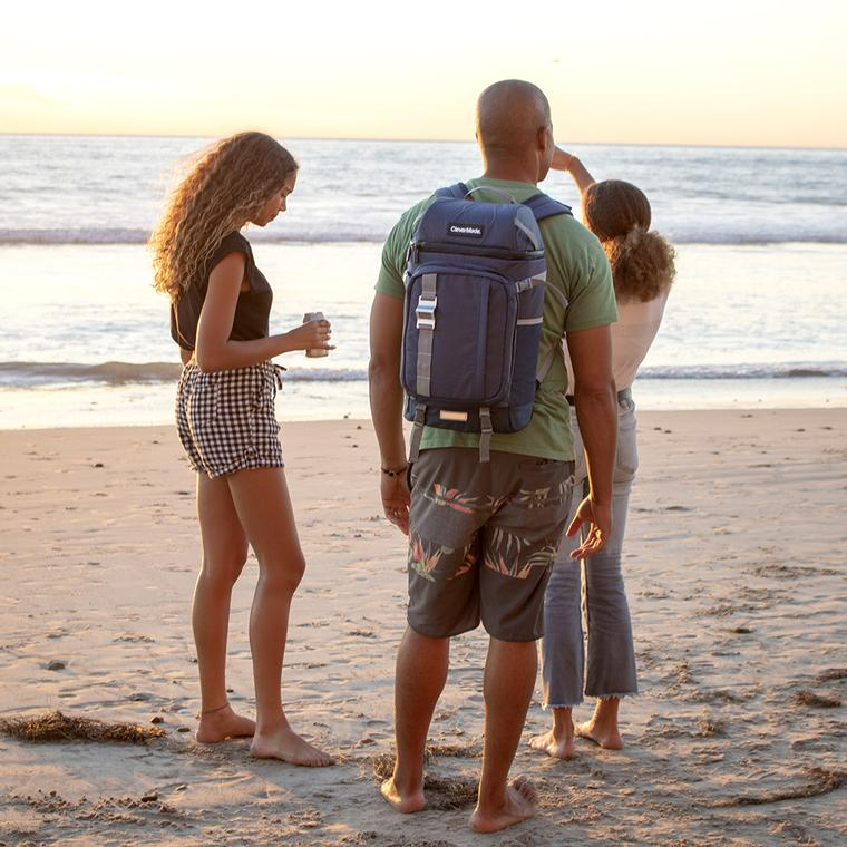 Young adults hanging out on the beach with the Cardiff Backpack Cooler