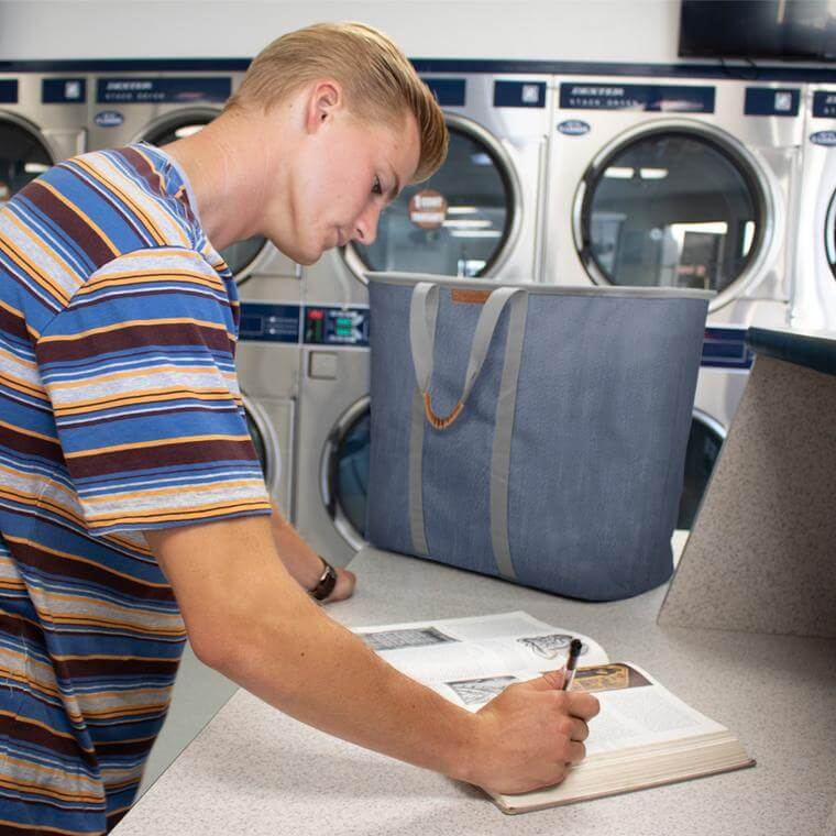 college student at the laundrymat with a Laundry Caddy LUXE