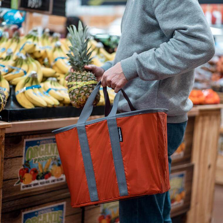 man grocery shopping carrying a SnapBasket Tote