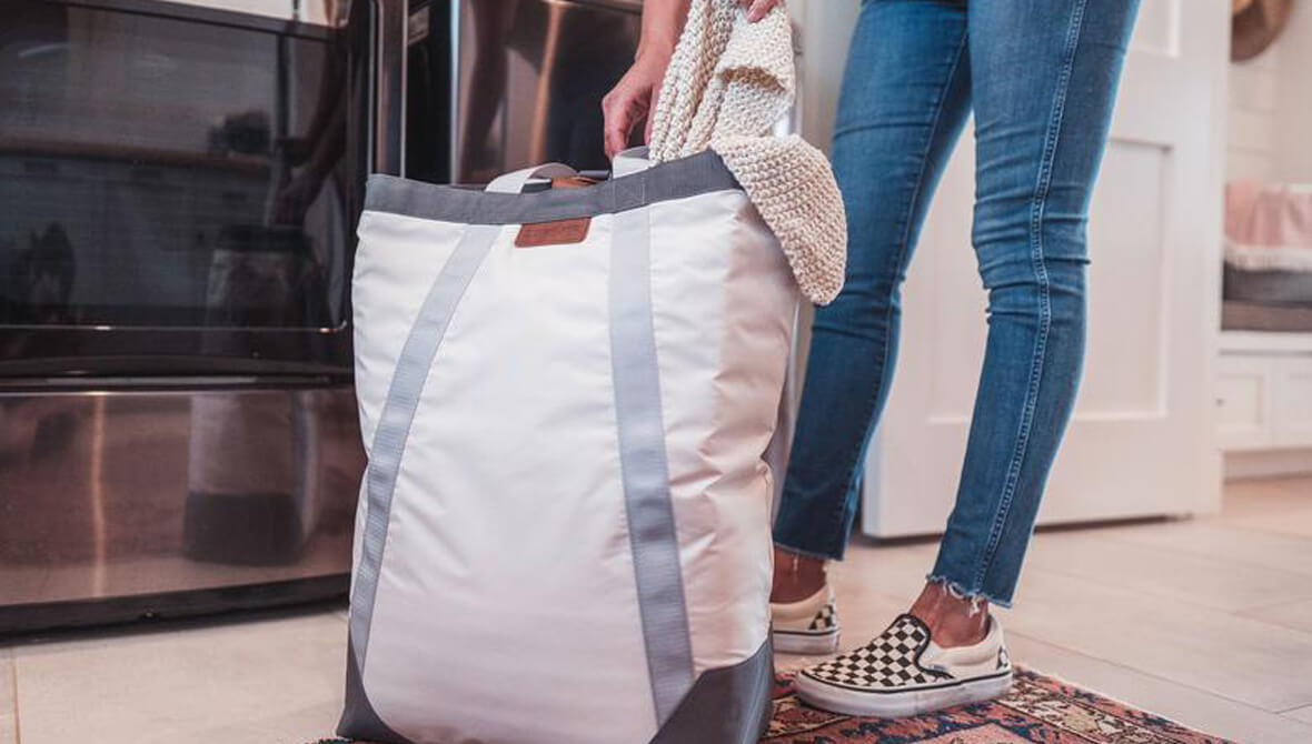 woman carrying the Laundry Backsack LUXE in Cream