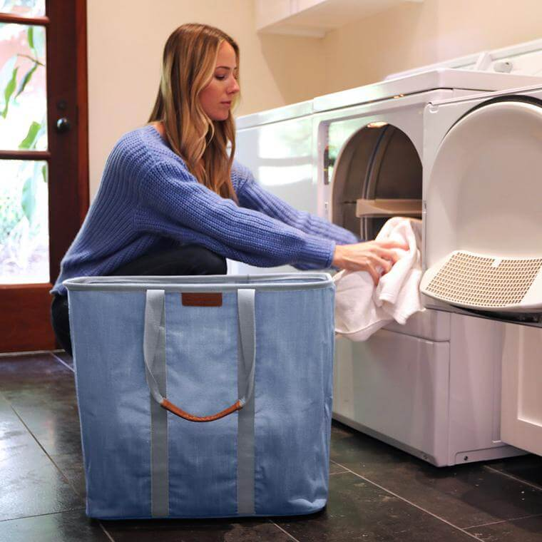 woman emptying clean laundry from dryer into a Laundry Caddy LUXE