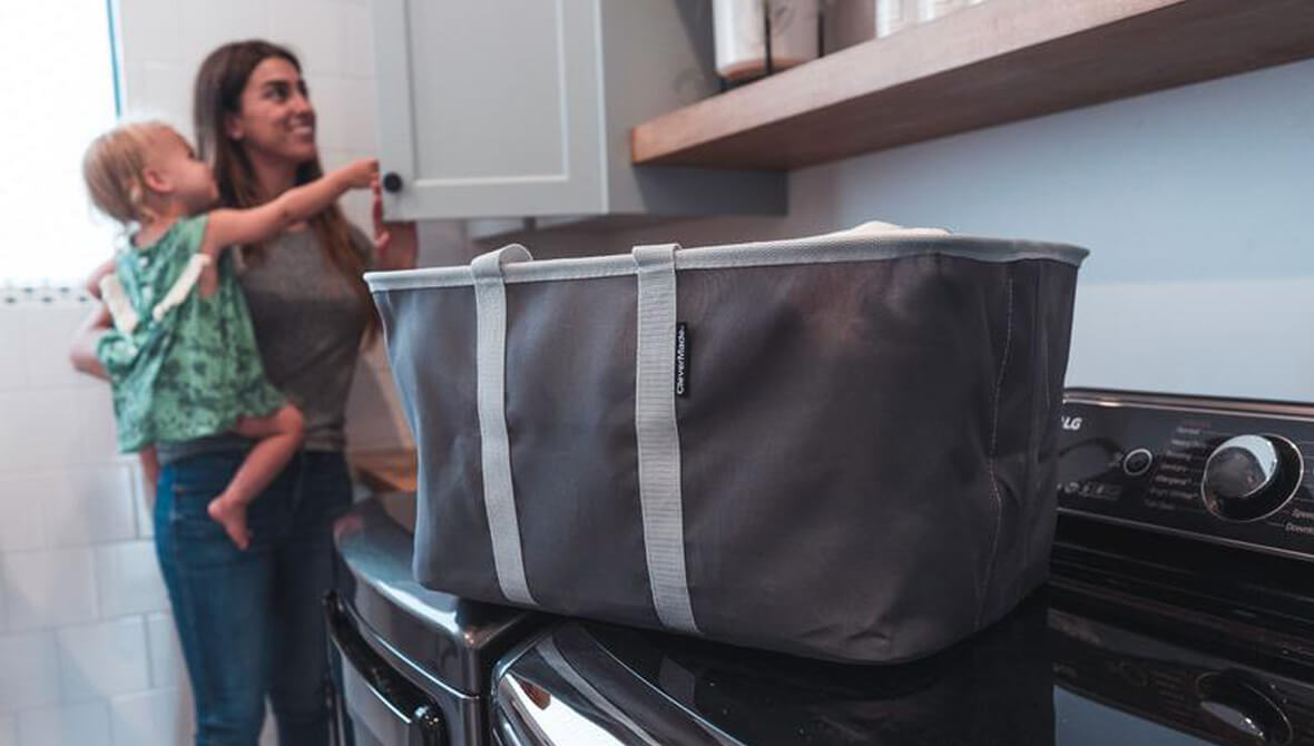 Mom holding child in the laundry room with a full Laundry Basket Tote