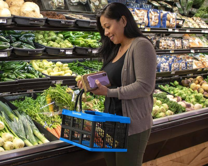 Woman shopping for vegetables using a CleverCrate® Shopping Basket