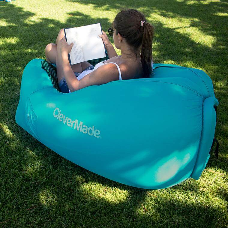 woman in park reading a book while sitting on the QuickFill AirChair Teal