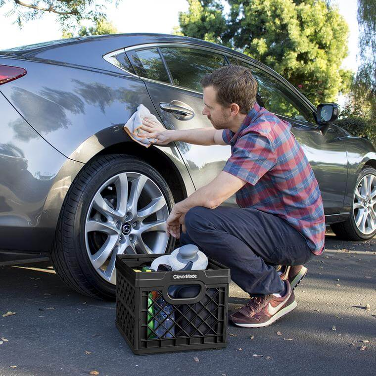 Man washing his car with a supplies in a CleverCrate® Milk Crate in Black