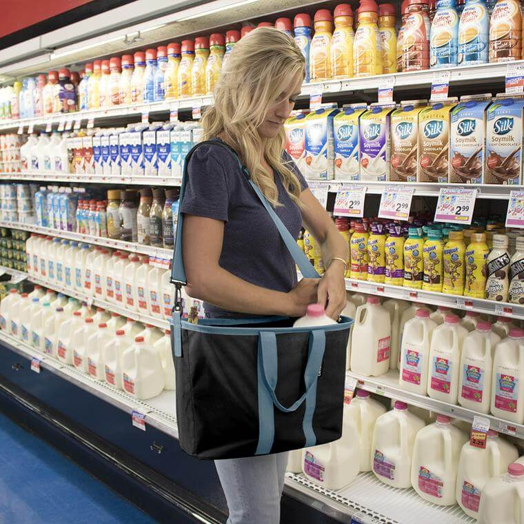 woman in the grocery store places milk in her EcoBasket
