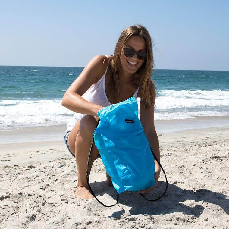 woman on beach pulling out the QuickFill AirChair from it's bag