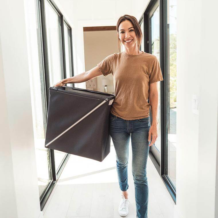 woman carrying a Quick Zip Hamper down the hall