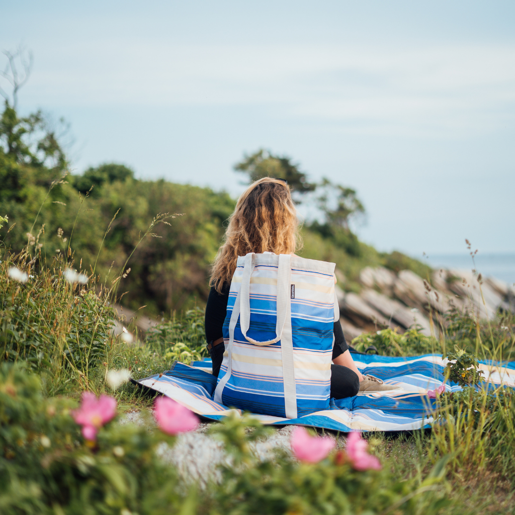 Girl sitting with the CleverMade BackSak Beach Tote
