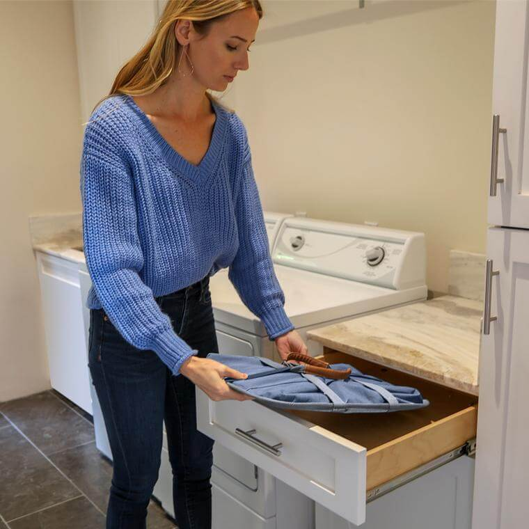woman storing the Laundry Caddy LUXE in a drawer