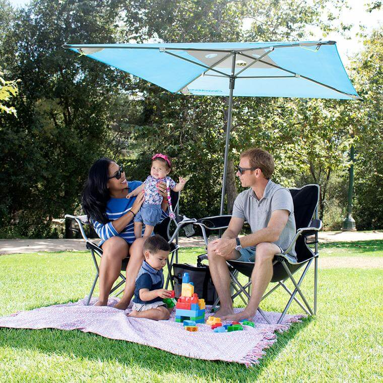 young family sitting under a QuadraBrella