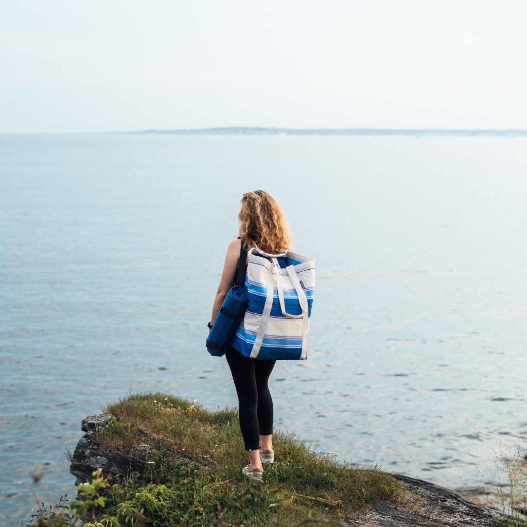 Girl standing on cliffside with the CleverMade BackSak Beach Tote on her back