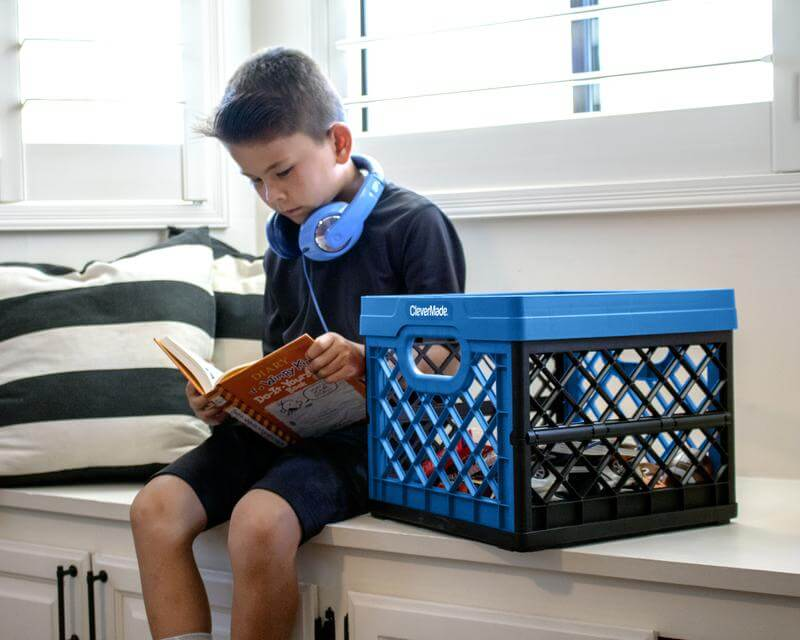 Young boy reading a book next to a CleverCrate® Milk Crate holding books