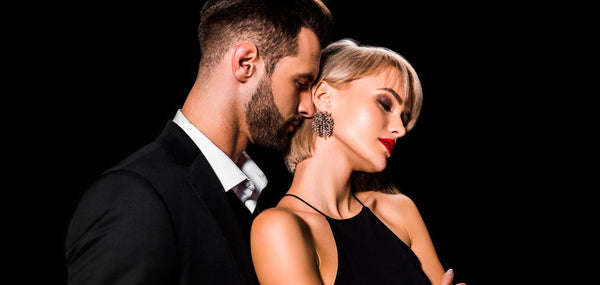 Women's perfumes that drive men crazy. Men and women dressed in black, elegant, on a black background. The man is behind the woman and smells her neck from behind. The woman bends her neck and closes her eyes.