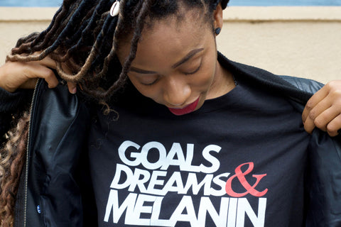 African Caribbean lady wearing a t-shirt with slogan Goals dreams and melanin
